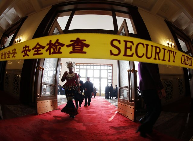 A minority delegate is seen behind security check line as she arrives for  the closing session of the National People's Congress (NPC), China's Parliament, at the Great Hall of the People, in Beijing, March 15, 2015. (Photo by Kim Kyung-Hoon/Reuters)