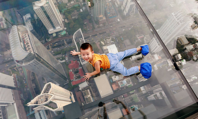 A boy plays on the glass at Thailand's first skywalk in Bangkok, Thailand on November 18, 2018. (Photo by Soe Zeya Tun/Reuters)