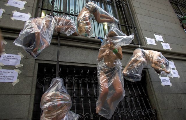 Women hanging in plastic bags perform during a protest against gender violence in Buenos Aires, Argentina, Wednesday, December 5, 2018. Argentine feminist groups and labor unions are protesting a court ruling that acquitted two men accused of sexually abusing and killing a 16-year-old girl. (Photo by Tomas F. Cuesta/AP Photo)
