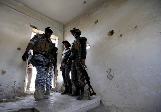 Iraqi security forces gather with their weapons at a building in Tikrit, March 27, 2015. (Photo by Thaier Al-Sudani/Reuters)