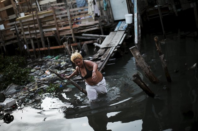 """Cheila, 33, wades through the water in front of her stilt house, a lake dwelling also known as palafitte or """"Palafito"""", in Recife, Brazil, February 8, 2016. (Photo by Nacho Doce/Reuters)"""
