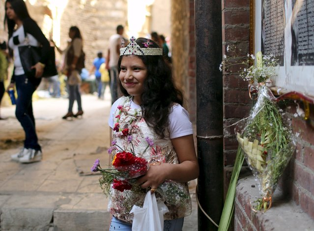 An Egyptian Coptic Christian girl carries flowers while wearing a palm decoration during Palm Sunday inside a Church in Old Cairo, April 5, 2015. (Photo by Asmaa Waguih/Reuters)