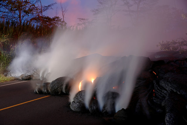 Volcanic gases rise from the Kilauea lava flow that crossed Pohoiki Road near Highway 132, near Pahoa, Hawaii, May 28, 2018. (Photo by Marco Garcia/Reuters)