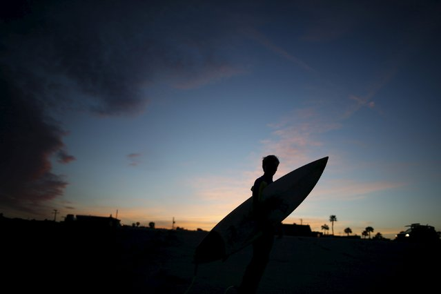 Reid Inskeep, 13, is silhouetted as he goes surfing before school at sunrise in Hermosa Beach, California March 24, 2015. (Photo by Lucy Nicholson/Reuters)