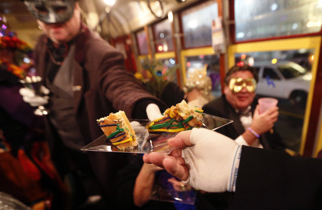 """Members of the """"Societe des Champs Elysee"""" pass out king cake as they ride the Rampart-St. Claude street car line, which just opened last fall, to commemorate the official start of Mardi Gras season, in New Orleans, Friday, January 6, 2017. (Photo by Gerald Herbert/AP Photo)"""