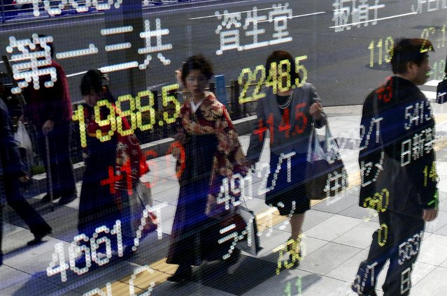 Women wearing Hakama, or Japanese traditional Kimono, are reflected in an electronic board, showing various stock prices, outside a brokerage in Tokyo, March 23, 2015. (Photo by Yuya Shino/Reuters)