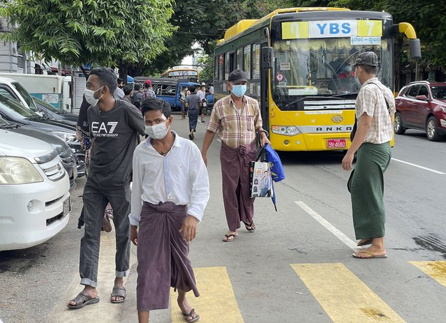 Commuters wearing face masks walk on a street after getting off a bus in Yangon, Myanmar, Thursday, July 8, 2021. Myanmar is facing a a rapid rise in COVID-19 patients and a shortage of oxygen supplies just as the country is consumed by a bitter and violent political struggle since the military seized power in February. (Photo by AP Photo/Stringer)