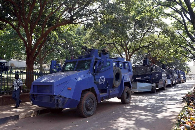 A man walks past police crowd control armored vehicles parked in Uganda's capital Kampala February 17, 2016, a day ahead of the presidential election. (Photo by James Akena/Reuters)