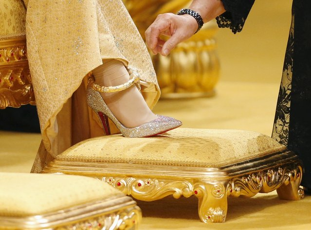 "A lady-in-waiting adjusts the dress and Christian Louboutin shoes of Dayangku Raabi'atul 'Adawiyyah Pengiran Haji Bolkiah as Adawiyyah waits for Prince Abdul Malik to arrive for the ""bersanding"" or enthronement ceremony at their wedding in the Nurul Iman Palace in Bandar Seri Begawan April 12, 2015. (Photo by Olivia Harris/Reuters)"