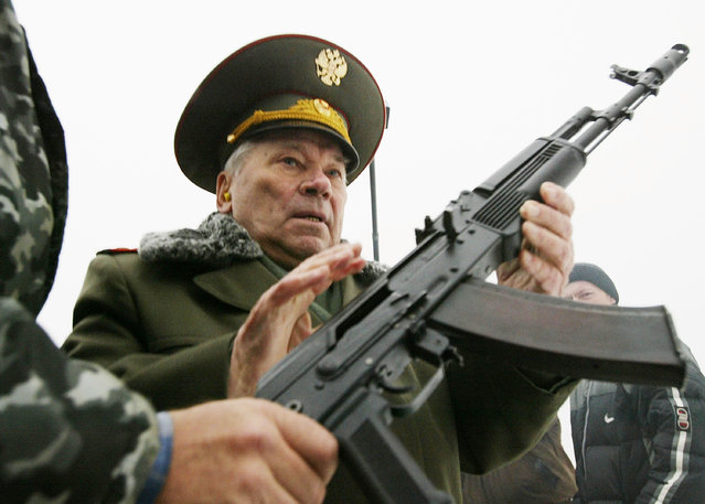 Mikhail Kalashnikov, the father of the world's most popular assault rifle, is handed  an AK-74 November 23, 2002 in Izhevsk,1000 East km. from Moscow. November 23 marked the 55th anniversary of the release of the first Kalashnikov gun. According to the Moscow-based Center for Analysis of Strategic and Technologies some 70 million to 100 million Kalashnikovs have been built worldwide since 1947, compared about 7 million to Kalashnikov's Western rival the M-16 assault rifles. (Photo by Oleg Nikishin/Getty Images)