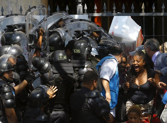 Squatters react as they are evicted from a abandoned building in Flamengo neighborhood, in Rio de Janeiro, April 14, 2015. (Photo by Ricardo Moraes/Reuters)