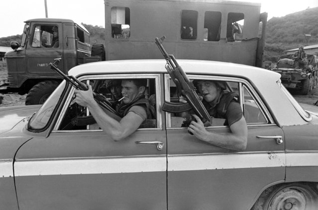 In this  October 27, 1983 file photo, soldiers brandish captured AK-47 rifles from the windows of a civilian vehicle as they drive near Point Salines Airport in St. George, Grenada. In 1983, U.S. forces invaded the Caribbean island of Grenada after accusing the government of allying itself with Communist Cuba. (Photo by Doug Jennings/AP Photo)