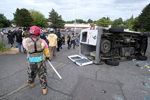 A van that was driven by anti-fascist protesters is pictured flipped on its side with all windows smashed after it was attacked for trying to drive into a Proud Boys rally Sunday, August 22, 2021, in Portland, Ore. (Photo by Alex Milan Tracy/AP Photo)
