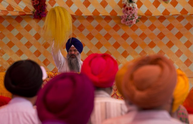 Indian Sikhs offer prayers at a Sikh temple on Baisakhi, in New Delhi, India, Tuesday, April 14, 2015. Baisakhi, the harvest festival celebrated in the Punjab region also coincides with other festivals celebrated on the first day of Indian calendar month Vaisakh. (Photo by Manish Swarup/AP Photo)