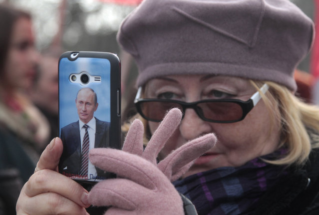 A portrait of Russian President Vladimir Putin is seen on a cover of a woman's phone as she takes pictures during celebrations of the Russian national holiday - Defender of the Fatherland Day in Sevastopol, Crimea, February 23, 2016. (Photo by Pavel Rebrov/Reuters)