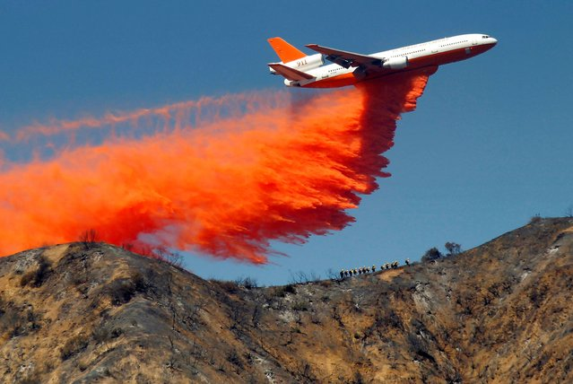 A DC-10 tanker drops fire retardant on a wildfire in the San Gabriel Mountains in Azusa, Calif., on Tuesday, September 24, 2013. (Photo by Nick Ut/AP Photo)