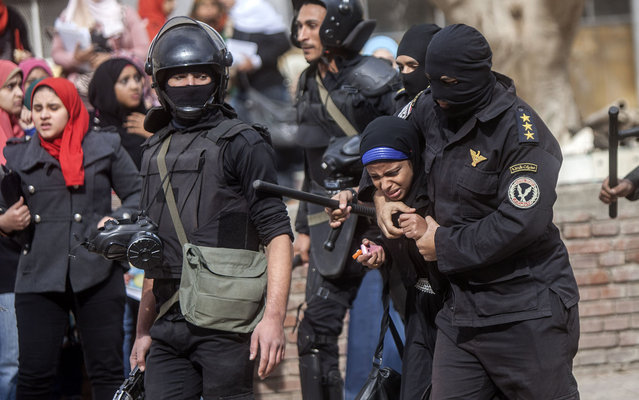 "An Egyptian riot policeman detains a female student of al-Azhar University during a protest by students who support the Muslim Brotherhood inside their campus in Cairo on December 30, 2013. Egypt urged Arab League members to enforce a counter terrorism treaty that would block funding and support for the Muslim Brotherhood after Cairo designated it as ""terrorist"" group. (Photo by Mahmoud Khaled/AFP Photo)"