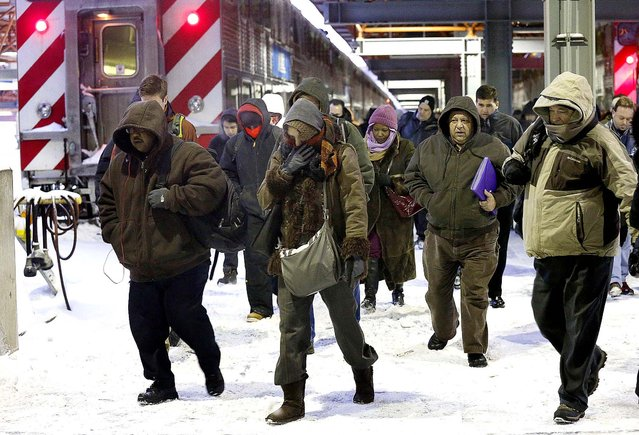 Commuters arrive at the La Salle Street commuter rail station as they experience temperatures well below zero and wind chills expected to reach 40 to 50 below in Chicago. (Photo by Charles Rex Arbogast/Associated Press)
