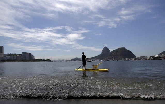 A man paddles his stand-up board at Botafogo Beach, located in Guanabara Bay, during a protest to call attention to pollution in its waters, where the Rio 2016 Olympic Games sailing events will take place in Rio de Janeiro, Brazil, February 27, 2016. (Photo by Ricardo Moraes/Reuters)