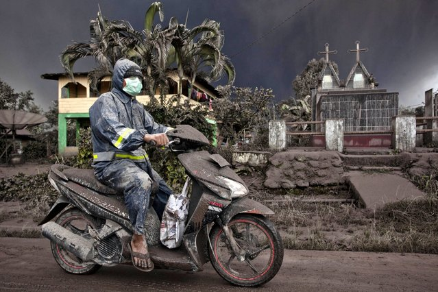 An ash covered a motorcyclist as drives on a road covered with ash following a further eruption of the Mount Sinabung on January 4, 2014 in Karo District, North Sumatra, Indonesia. The number of displaced persons has increased to 20,000 in Western Indonesia as Mount Sinabung continues to spew ash and smoke after several eruptions since September. (Photo by Ulet Ifansasti/Getty Images)