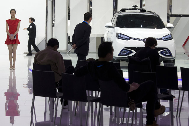 A Chinese woman waits to help attendee understand the MG car on display at the Shanghai Auto Show in Shanghai, Monday, April 20, 2015. (Photo by Ng Han Guan/AP Photo)