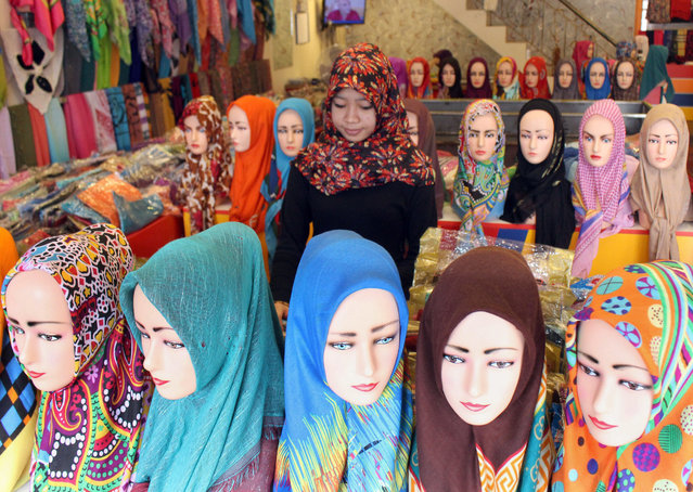 An Indonesian vendor waits for customer at a hijab store in Jakarta, Indonesia, 09 April 2015. (Photo by Adi Weda/EPA)