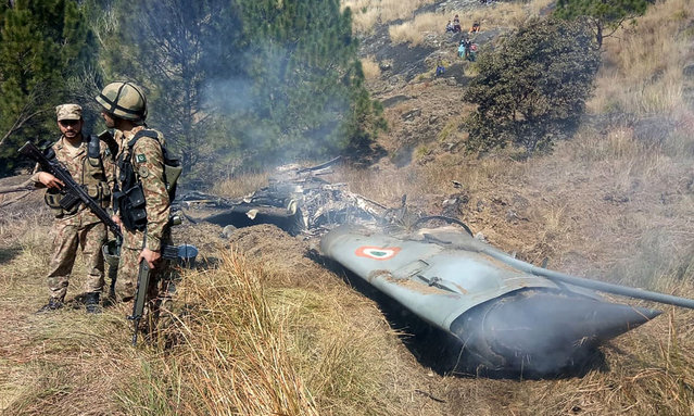 Pakistani soldiers stand next to what Pakistan says is the wreckage of an Indian fighter jet shot down in Pakistan controled Kashmir at Somani area in Bhimbar district near the Line of Control on February 27, 2019. Pakistan said on February 27 it shot down two Indian warplanes in its airspace over disputed Kashmir, in a dramatic escalation of a confrontation that has ignited fears of an all-out conflict between the nuclear-armed neighbours. (Photo by AFP Photo/Stringer)