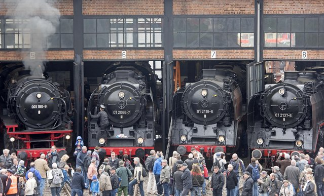 Visitors  stand in front of steam locomotives during the Dresden Steam Locomotive Festival, the biggest steam engine spectacle in Germany, in the maintenance depot of the railway museum  in Dresden, eastern Germany, Saturday, April 18, 2015. (Photo by Jens Meyer/AP Photo)