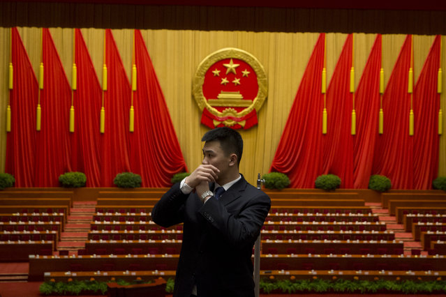 In this Saturday, March 5, 2016 photo, a security guard talks into a microphone attached in his sleeve as he clears the hall after the opening session of the National People's Congress (NPC) at the Great Hall of the People in Beijing. Unlike legislatures elsewhere, China's does little in the way of legislating, is carefully stage-managed and allows no foreign leader to address it. But like such chambers of power elsewhere, China's has become something of a billionaire's club, where the super-rich sit shoulder-to-shoulder with colorfully adorned Tibetan, Mongolian and other minority delegates and members of the country's vast bureaucracy. (Photo by Ng Han Guan/AP Photo)