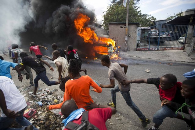 Demonstrators run away from police who are shooting in their direction, as a car burns during a protest demanding the resignation of Haitian President Jovenel Moise in Port-au-Prince, Haiti, Tuesday, February 12, 2019. (Photo by Dieu Nalio Chery/AP Photo)