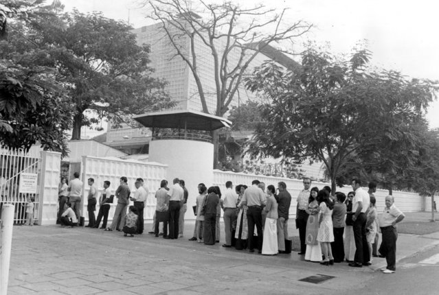 Americans and their South Vietnamese dependents wait in line outside the U.S. consulate to apply for visas in Saigon, Vietnam, Saturday, April 5, 1975. (Photo by AP Photo)