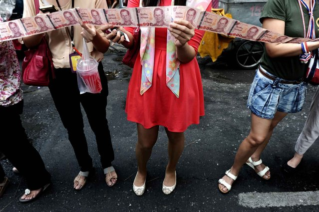 Supporters hold bank notes to donate to protest leader Suthep Thaugsuban (not pictured) during an anti-government march in downtown Bangkok on February 7, 2014. Thai anti-government protesters vowed to press on with street rallies aimed at ousting Prime Minister Yingluck Shinawatra after a disrupted election failed to cut a path through the kingdom's political crisis. (Photo by Christophe Archambault/AFP Photo)