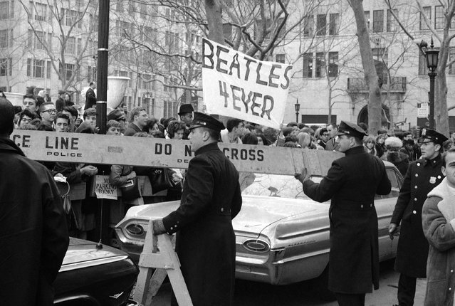 Police man the barricades outside New York's Plaza Hotel, on February 7, 1964, as Beatle maniacs push forward in hopes of a view of Britain's singing sensations after their arrival for an American tour. (Photo by AP Photo)