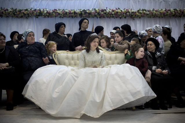 A Jewish bride sits with family members in the women's section during her wedding to the grandson of the Rabbi of the Tzanz Hasidic dynasty community, in Netanya, Israel, Tuesday, March 15, 2016. (Photo by Oded Balilty/AP Photo)