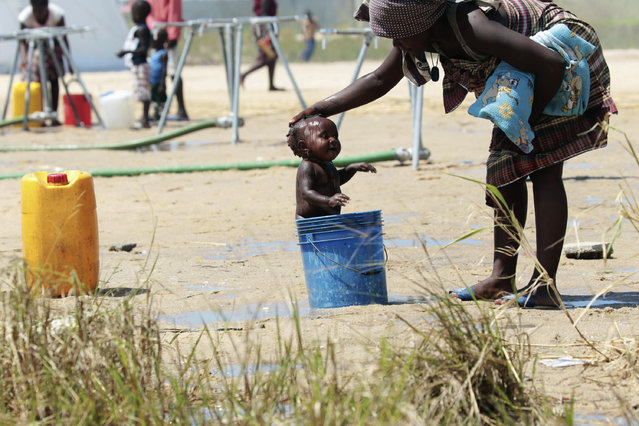 A mother bathes her baby in a bucket at a camp for displaced survivors of Cyclone Idai in Beira, Mozambique, Sunday, March, 31, 2019. Cholera cases among cyclone survivors in Mozambique have jumped to 271, authorities said. So far no cholera deaths have been confirmed, the report said. Another Lusa report said the death toll in central Mozambique from the cyclone that hit on March 14 had inched up to 501. Authorities have warned the toll is highly preliminary as flood waters recede and reveal more bodies. (Photo by Tsvangirayi Mukwazhi/AP Photo)
