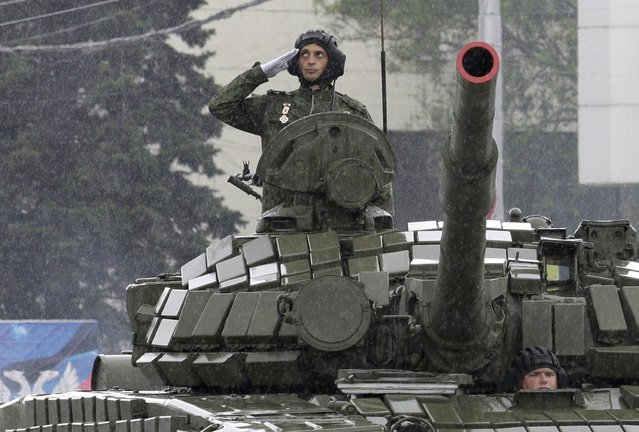 """Pro-Russian separatist commander Mikhail Tolstykh, known by the nom de guerre """"Givi"""", salutes atop of a tank during the Victory Day parade, marking the 70th anniversary of the victory over Nazi Germany in World War Two, in Donetsk, Ukraine May 9, 2015. A separatist commander in the eastern Ukrainian region of Donetsk has been assassinated, the Russia-backed separatists say. Mikhail Tolstykh, better known by his nom de guerre Givi, died after a bomb exploded in his office in the separatist stronghold of Donetsk just after 6 a.m. local time on February 8, de facto separatist authorities and a source with ties to its military told RFE/RL by phone. The separatists announced two days of mourning. Donetsk separatist leaders called the killing a """"terrorist"""" attack organized by the Ukrainian intelligence services. (Photo by Alexander Ermochenko/Reuters)"""