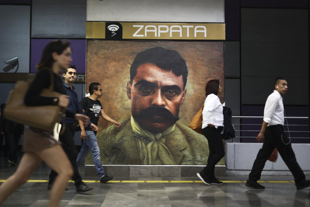 People pass an image of Mexican revolutionary leader Emiliano Zapata on exhibit at the Zapata metro station in Mexico City, Wednesday, April 10, 2019. Mexico marked the 100th anniversary on Wednesday of the assassination of Zapata, one of the main heroes of the 1910-1917 revolution who was gunned down by government soldiers over his unyielding defense of peasants. (Photo by Eduardo Verdugo/AP Photo)