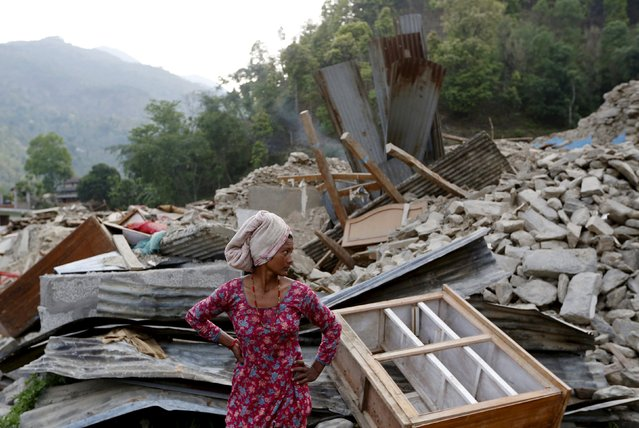 A woman dries her hair as she stands amongst the ruins of a building destroyed by the earthquake, near Laharepauwa, Nepal, May 5, 2015. (Photo by Olivia Harris/Reuters)