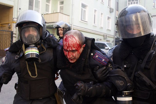 Policeman evacuate a wounded colleague during clashes with anti-government protesters in Kiev, on February 18, 2014. (Photo by Anatolii Stepanov/AFP Photo)