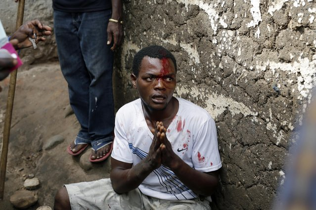 Jean Claude Niyonzima, a suspected member of the ruling party's Imbonerakure youth militia, pleads for his life as he is surrounded at his house by demonstrators protesting President Pierre Nkurunziza's decision to seek a third term in office in the Cibitoke district of Bujumbura, Burundi, Thursday May 7, 2015. (Photo by Jerome Delay/AP Photo)