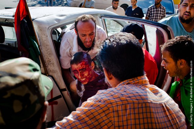 A Libyan Rebel soldier, wounded in battle against pro-Gaddafi loyalists, is unloaded by a fellow fighter at the Tripoli Central Hospital