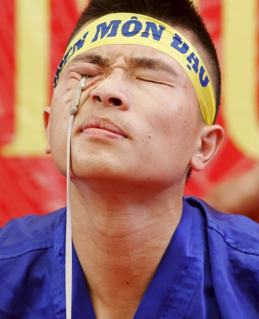 Do Dang Tuan uses his right eyelids to pull up a bucket of water attached to a rope, as he performs during a showcase of traditional Thien Mon Dao kung fu at Du Xa Thuong village, southeast of Hanoi, Vietnam May 10, 2015. (Photo by Reuters/Kham)