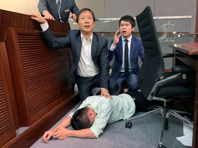 Pro-democracy lawmaker Gary Fan lies down after clashes with pro-Beijing lawmakers during a meeting for control of a meeting room to consider the controversial extradition bill, in Hong Kong, China on May 11, 2019. (Photo by James Pomfret/Reuters)
