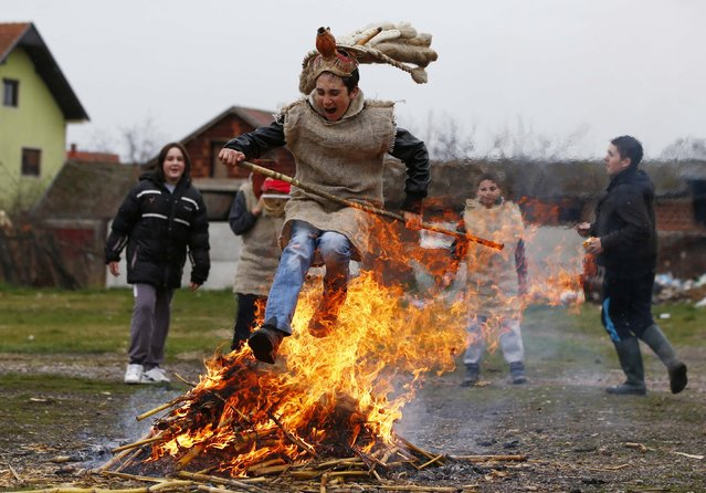 A boy wearing a mask jumps over the fire during Bele Poklade carnival celebrations in the village of Lozovik, some 100 km (62 miles) from the capital Belgrade, March 2, 2014. Bele Poklade has its roots in old pagan customs and is marked annually seven weeks before Easter. Children walk through the village to collect eggs, and at the end they jump over a fire to banish evil demons. (Photo by Marko Djurica/Reuters)