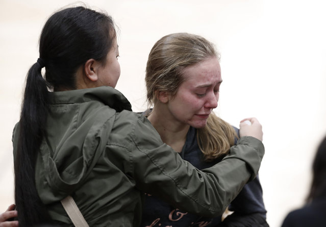 Young women console each other during a community vigil to honor the victims and survivors of yesterday's fatal shooting at the STEM School Highlands Ranch, Wednesday, May 8, 2019, in Highlands Ranch, Colo. (Photo by David Zalubowski/AP Photo)