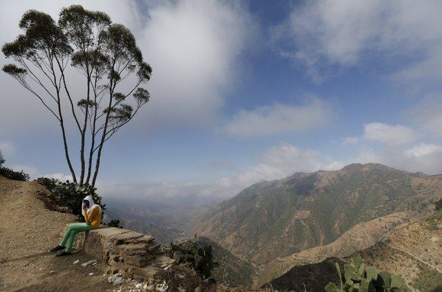A woman sits next to an escarpment on the outskirts of Asmara, Eritrea, February 20, 2016. (Photo by Thomas Mukoya/Reuters)