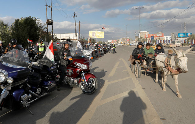 Members of the Iraq Bikers are seen with their motorbikes on a street of Baghdad, December 28, 2018. But riding a chopper through Baghdad is quite different from Route 101. The bikers have to slow down at the many military checkpoints set up around the city to deter suicide and car bomb attacks. And very few can afford a top bike. (Photo by Thaier Al-Sudani/Reuters)