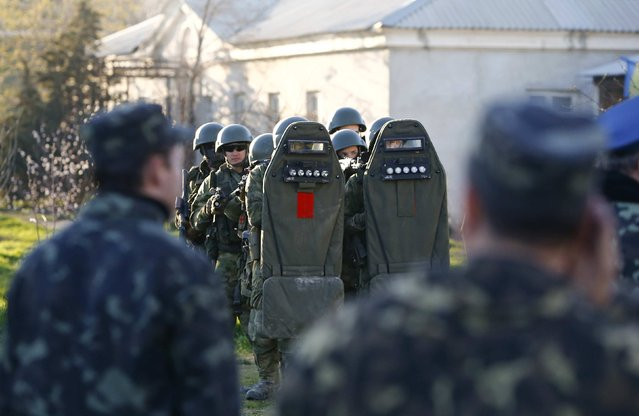 Armed men, believed to be Russian servicemen, stand guard, with Ukrainian servicemen seen in the foreground, at a military airbase, in the Crimean town of Belbek near Sevastopol March 22, 2014. Russian troops forced their way into a Ukrainian airbase in Crimea with armored vehicles, automatic fire and stun grenades on Saturday, injuring a Ukrainian serviceman and detaining the base's commander for talks. (Photo by Shamil Zhumatov/Reuters)