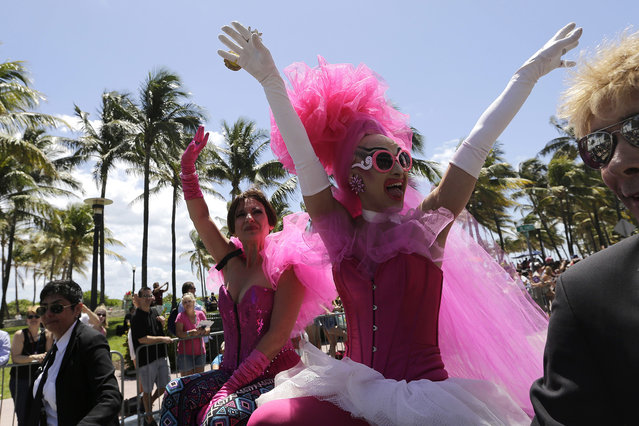 A performer named Adore, right, waves to the crowd during a parade along Ocean Drive at Miami Beach Gay Pride, Sunday, April 10, 2016, in Miami Beach, Fla. The annual event is meant to bring together members of the LGBT community, along with friends, families, and their supports. (Photo by Lynne Sladky/AP Photo)