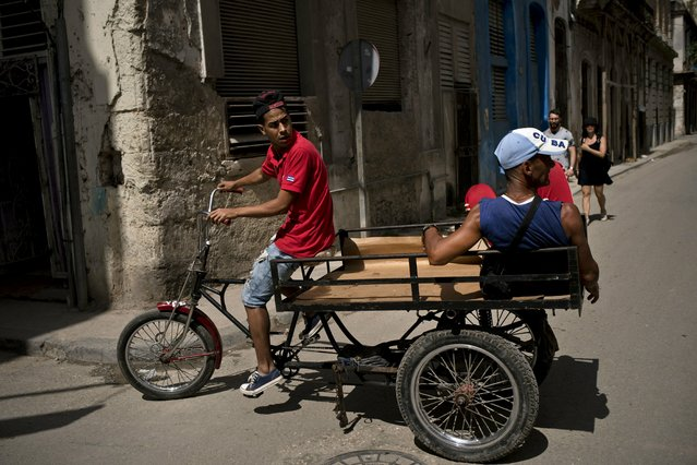 A man pedaling a tricycle equipped with a platform earns a living by transporting passengers through Havana, Cuba, Wednesday, April 10, 2019. (Photo by Ramon Espinosa/AP Photo)